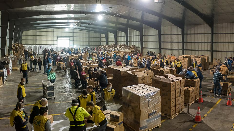 Latter-day Saint volunteers package and distribute goods and supplies
